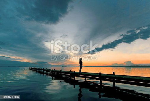Silhouette of woman standing on lakeside jetty at dusk watching majestic cloudscape. Location: Lake Steinhuder Meer, Lower Saxony, Germany.