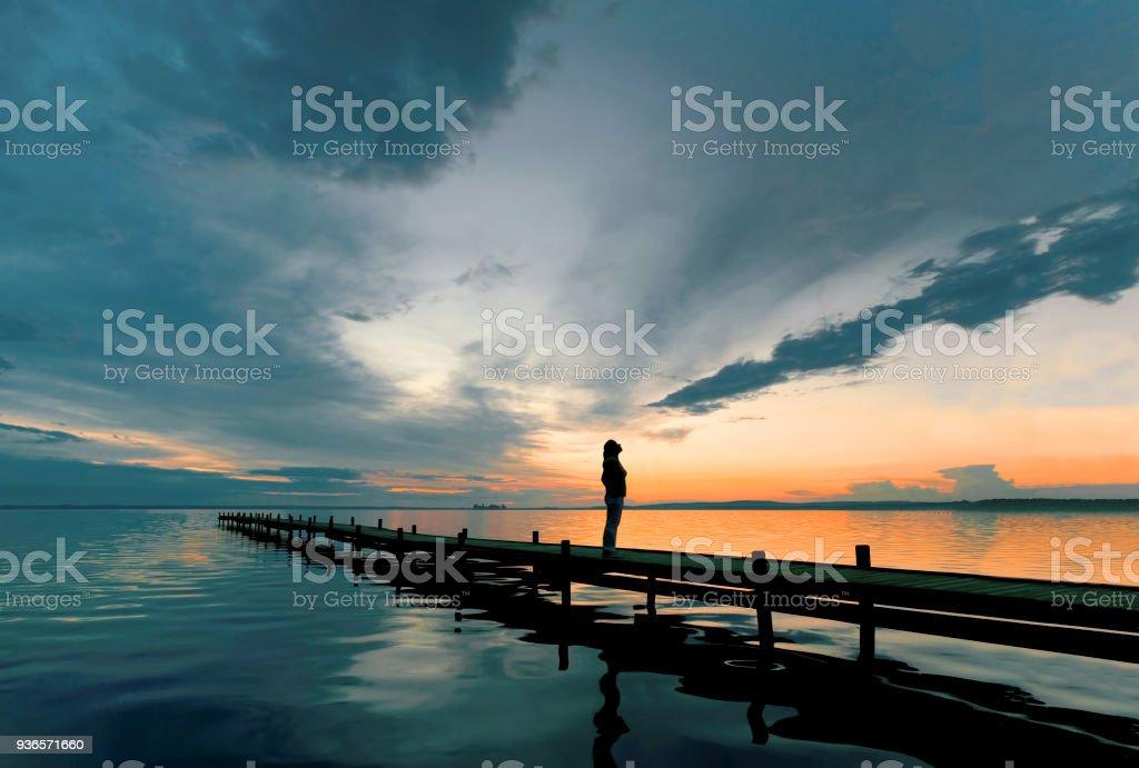 Silhouette der Frau auf See Anlegestelle in Abenddämmerung beobachten majestätische Wolkengebilde – Foto