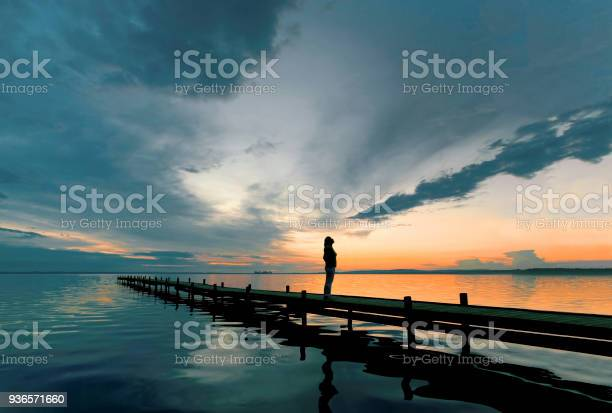 Photo of Silhouette of woman standing on lakeside jetty at dusk watching majestic cloudscape