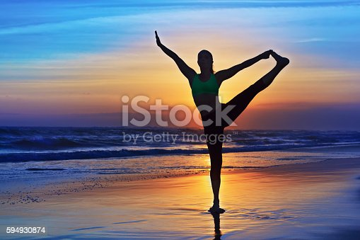 583830686istockphoto Silhouette of woman stretching at yoga retreat on sunset beach 594930874