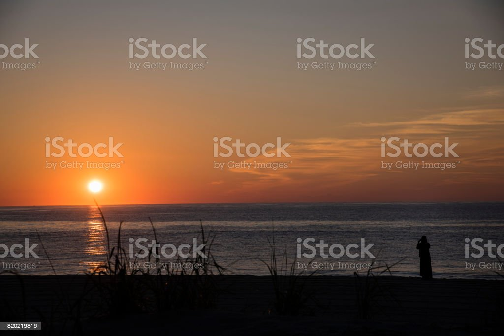 Silhouette of Woman Taking Photo of Sunrise on Bethany Beach stock photo