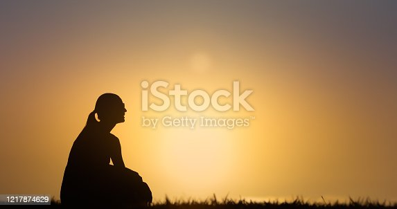 500841556 istock photo Silhouette of woman thinking watching the sunset. 1217874629