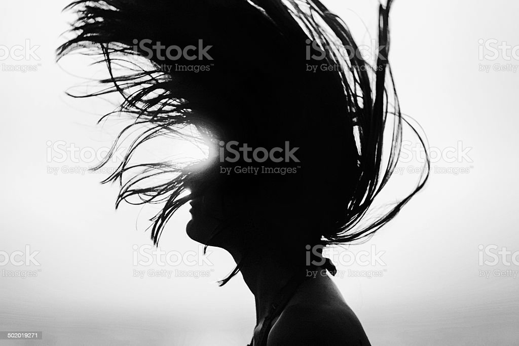 Silhouette of woman tossing hair at sunset black and white stock photo