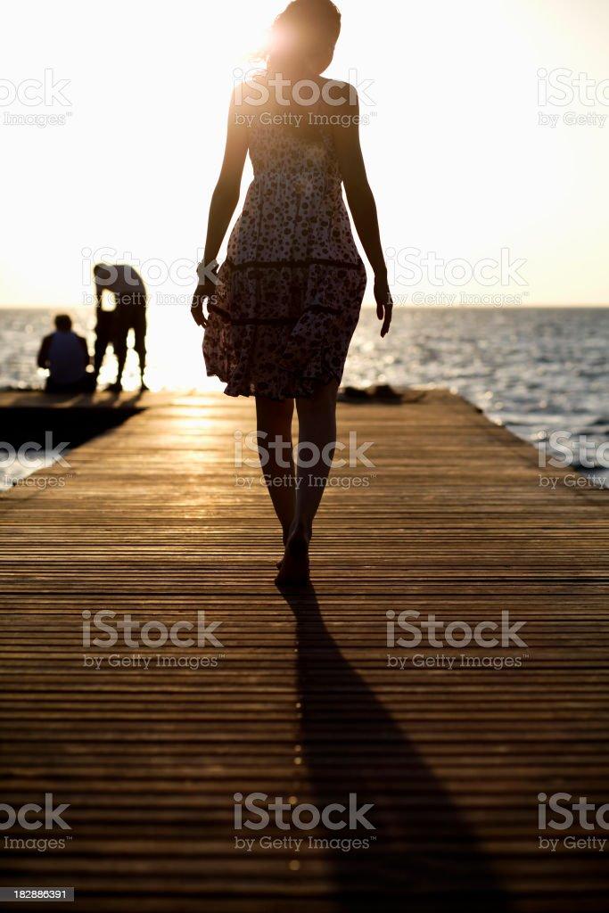 Silhouette of woman walking on dock in sunlight stock photo