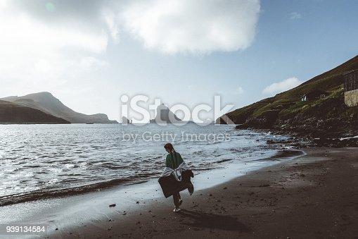 619670604 istock photo Silhouette of Woman walking on the black sand beach in Faroe Islands 939134584