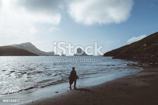 619670604 istock photo Silhouette of Woman walking on the black sand beach in Faroe Islands 939134612