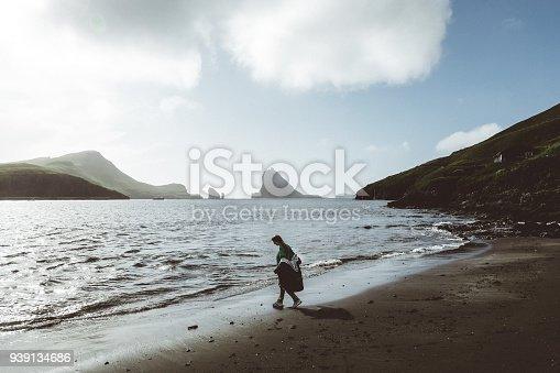 619670604 istock photo Silhouette of Woman walking on the black sand beach in Faroe Islands 939134686