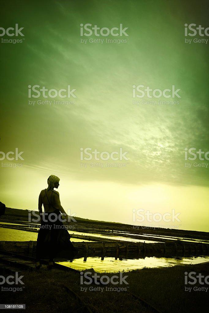 Silhouette of Woman Walking Through Slovenian Salterns royalty-free stock photo
