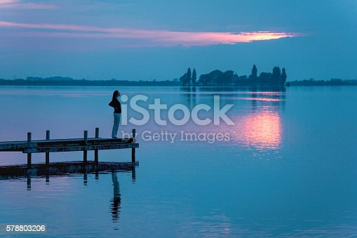 istock Silhouette of Woman Watching Sunset Reflection on Lakeside Jetty 578803206