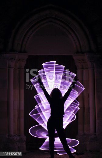 Curved abstract shape made with a light saber violet. Lightpainting session at night.