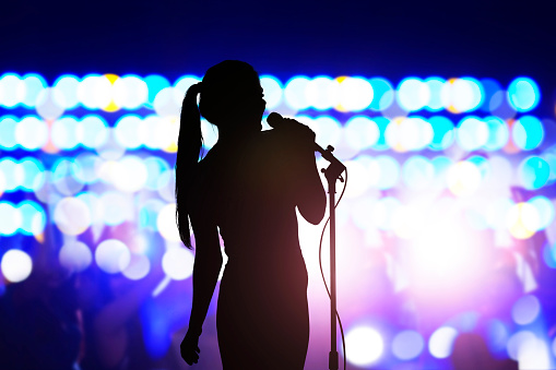 Silhouette of woman with microphone singing on concert stage in front of crowd