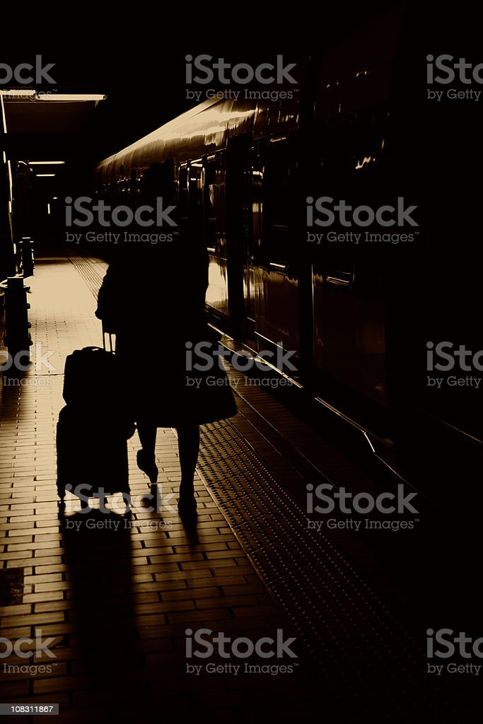Silhouette of woman with travel case on train platform royalty-free stock photo