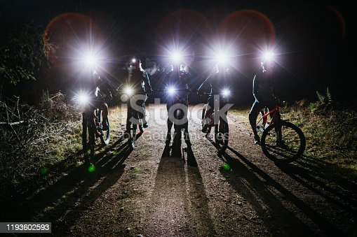 An all female mountain bike team enjoys a ride on some forest trails at night, equipped with bright head lamps and bike lights.   Shot in Washington State on the Olympic Peninsula.