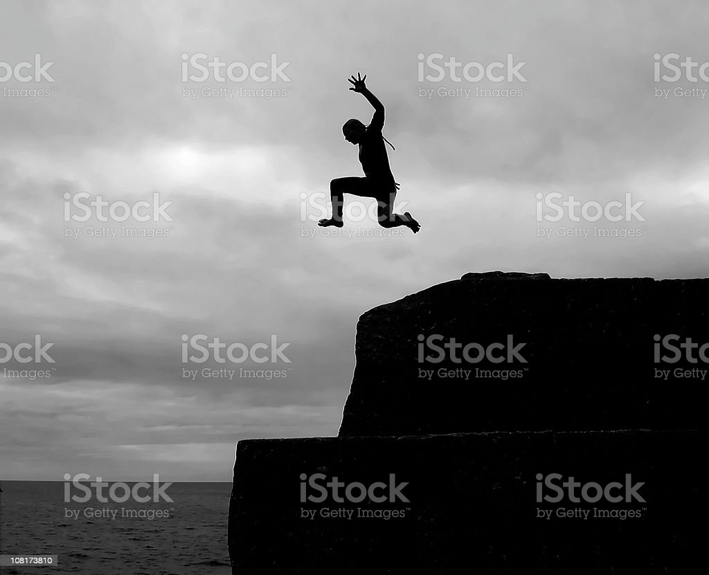 I CAN FLY! Silhouette of young Boy Cliff Diving royalty-free stock photo
