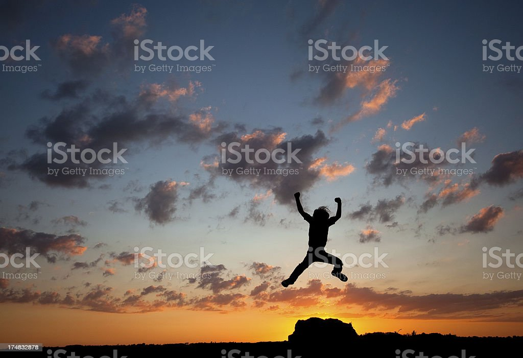 Silhouette of Young Boy Jumping stock photo
