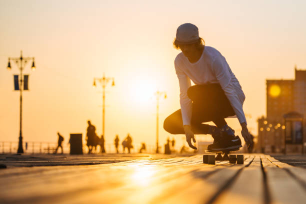 Silhouette of young boy riding longboard on the boardwalk, warm summer time sunset stock photo