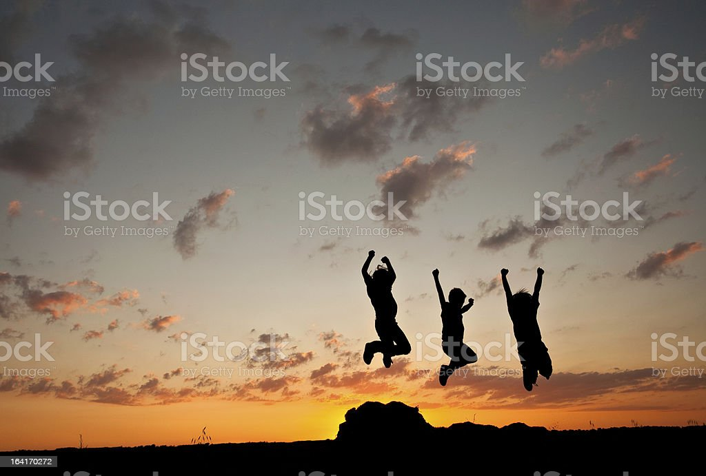 Silhouette of Young Boys Jumping stock photo
