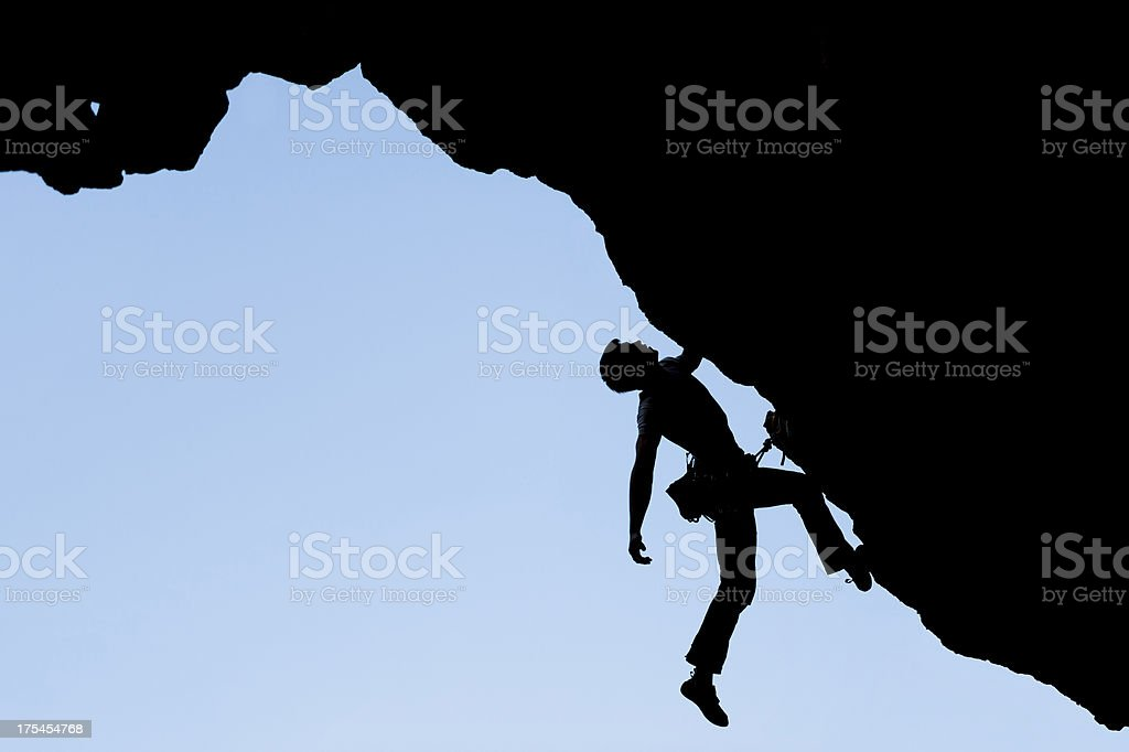 Silhouette of young climber in the rock wall royalty-free stock photo