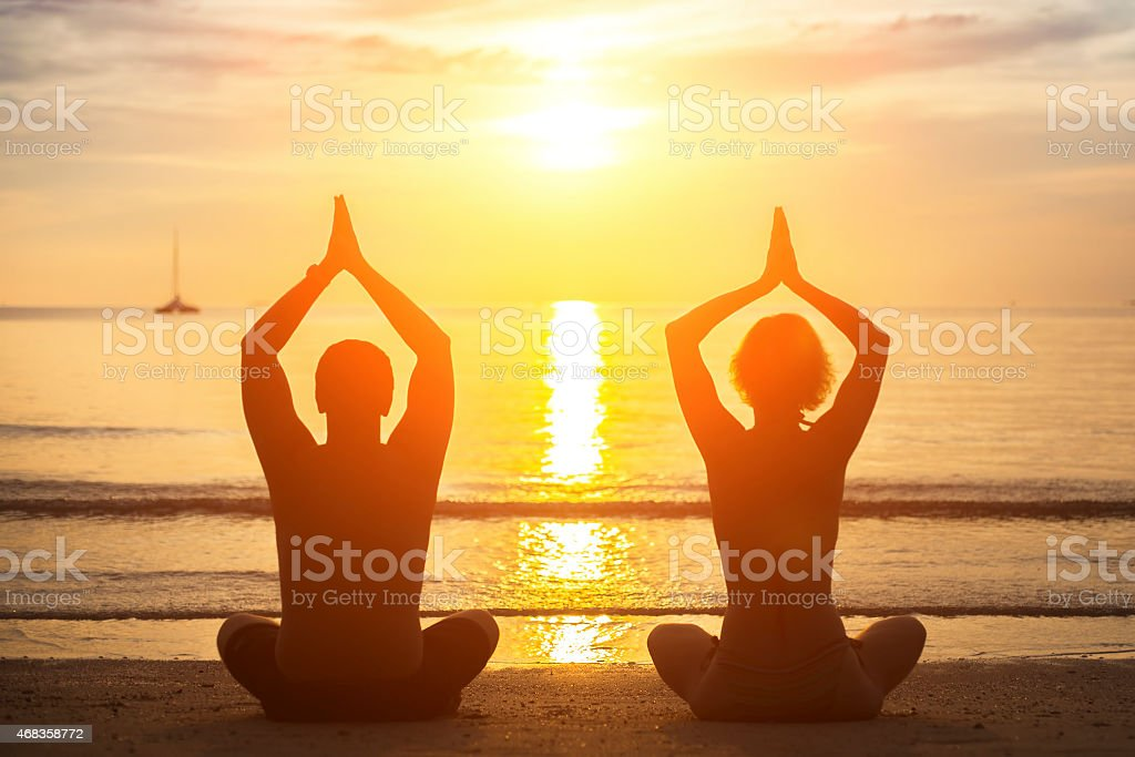 Silhouette of young couple practicing yoga on the beach. royalty-free stock photo