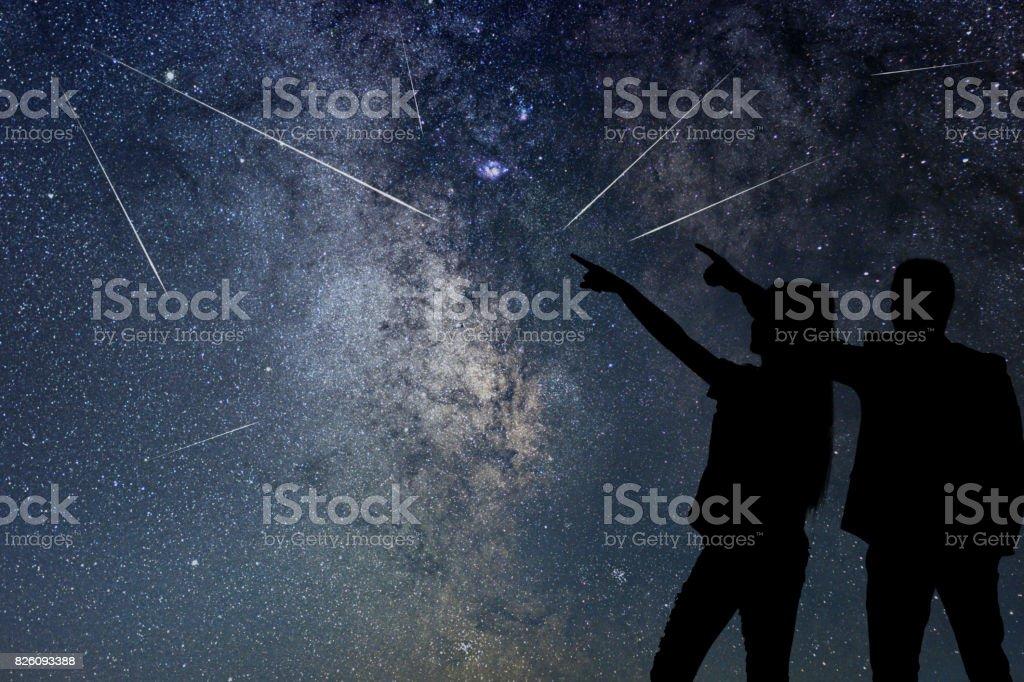 Silhouette des jungen Paares Meteorschauer beobachten. Nahe Himmel. – Foto