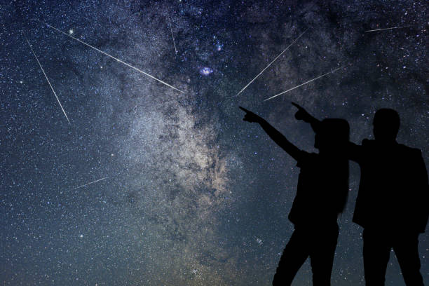 Silhouette of young couple watching Meteor Shower. Nigh Sky. stock photo