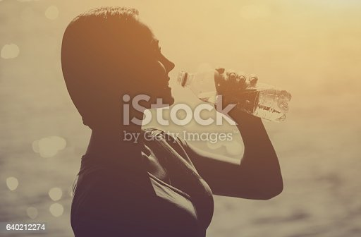 638628530 istock photo Silhouette of young female athlete drinking water. 640212274