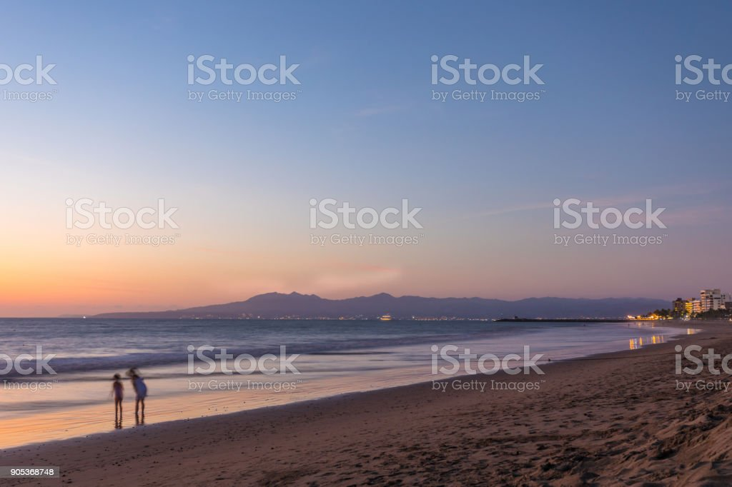 silhouette of young friends at the beach during sunset stock photo
