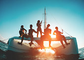 Silhouette of young friends chilling in catamaran boat - Group of people making tour ocean trip - Travel, summer, friendship, tropical concept - Focus on two left guys - Water on camera