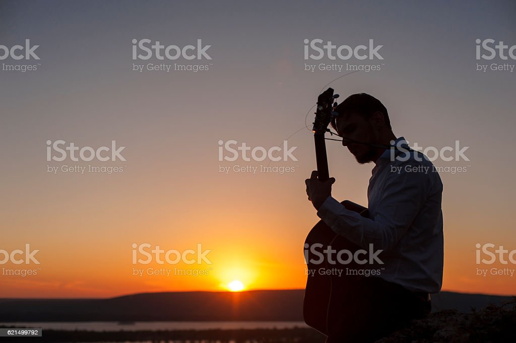 Silhouette of young guitar player at sunset photo libre de droits