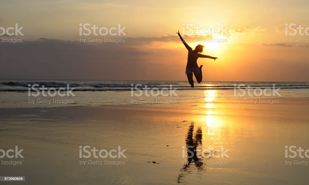 Silhouette of young happy Asian woman in bikini jumping excited on sunset beach having fun in healthy lifestyle stock photo