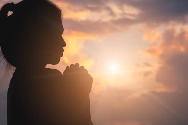 silhueta de mãos humanas jovens orando a deus, ao nascer do sol, fundo do conceito de christian religion. - cristianismo - fotografias e filmes do acervo