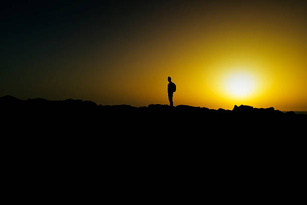 silhouette of young man at dusk stock photo