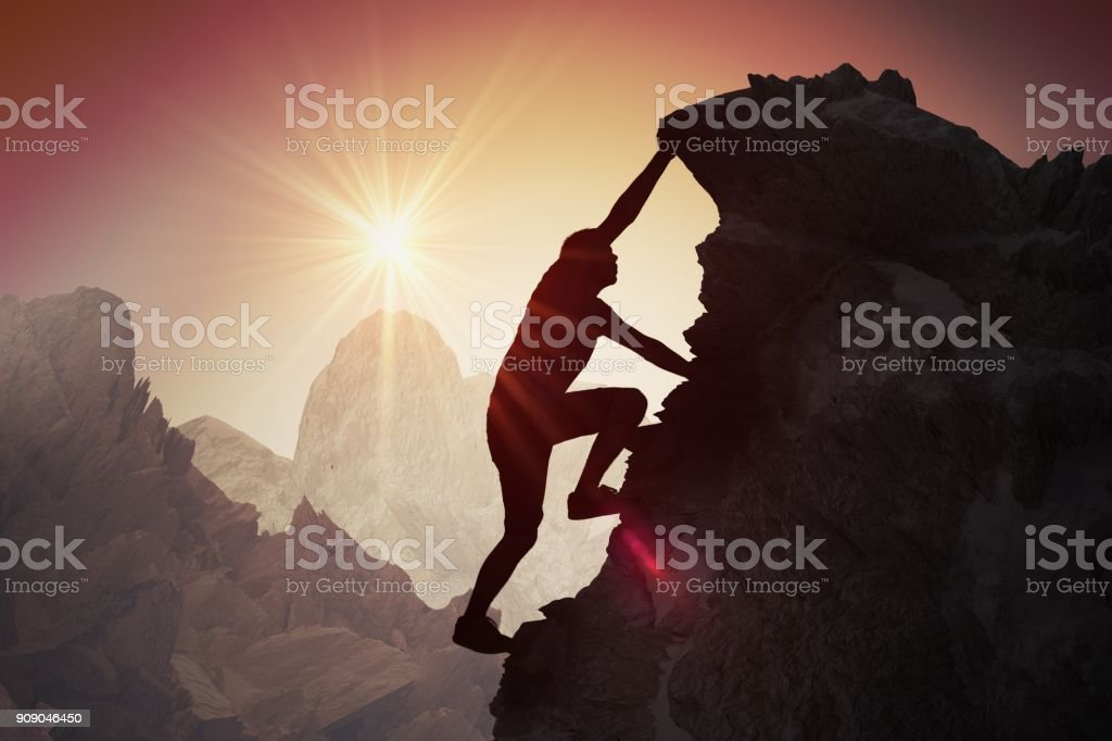 Silhouette of young man climbing on mountain. stock photo