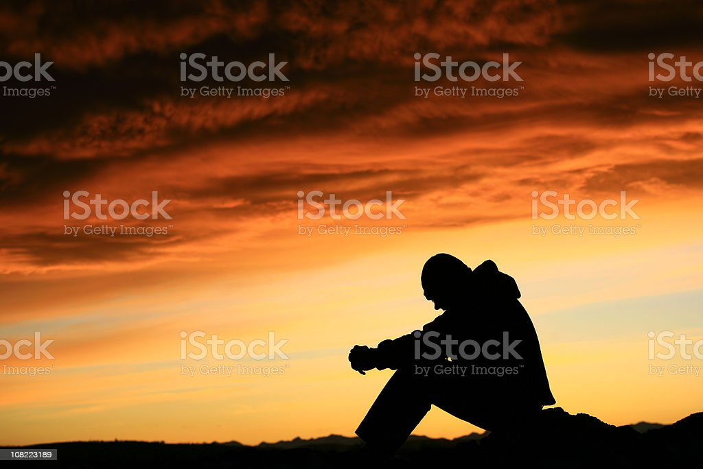 Silhouette of Young Man Contemplating Life stock photo