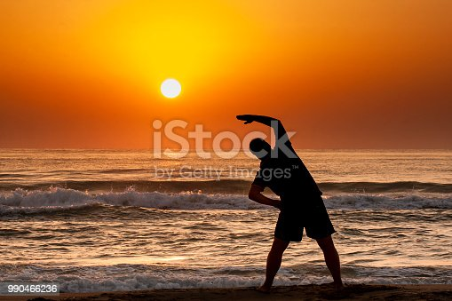 Silhouette of young man doing fitness exercise on the beach at sunrise or sunset