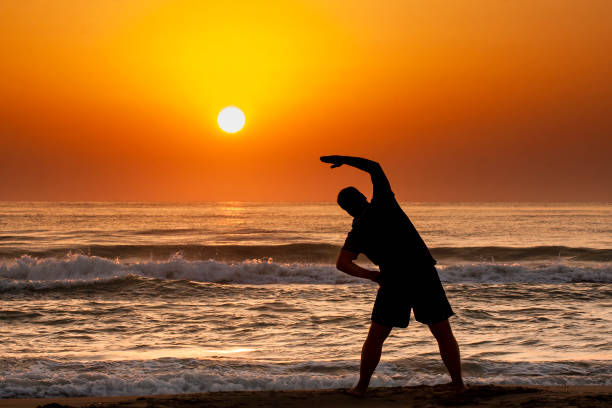 Silhouette of young man doing fitness exercise on the beach at sunrise or sunset stock photo