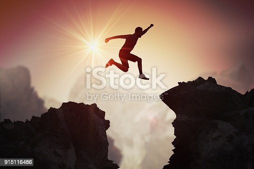 Silhouette of young man jumping over mountains and cliffs at sunset.