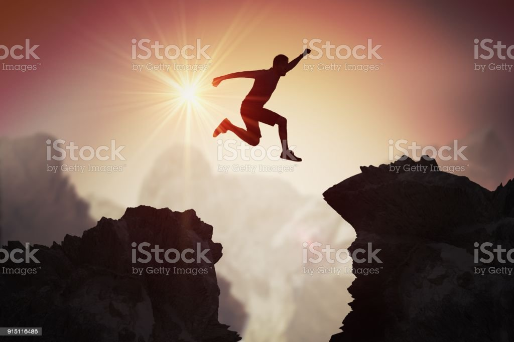 Silhouette of young man jumping over mountains and cliffs at sunset. stock photo