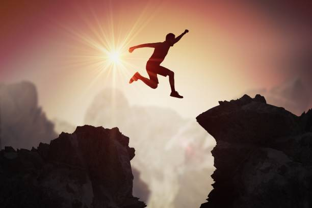 silhouette of young man jumping over mountains and cliffs at sunset. - disconnect stock pictures, royalty-free photos & images