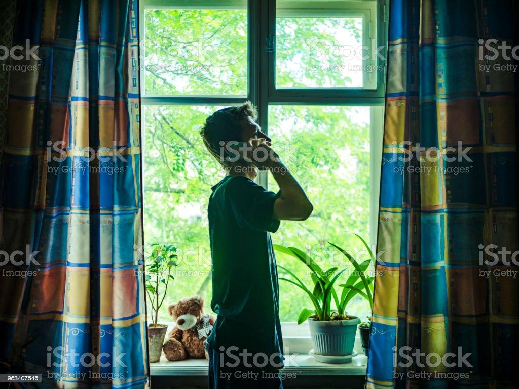 silhuetten av ung man nära fönstret talar med sin telefon på morgonen - Royaltyfri Affärsman Bildbanksbilder