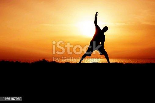 Silhouette of Young Man Practicing Yoga. Sunset on the Seacoast. Trikonasana, Triangle Pose.