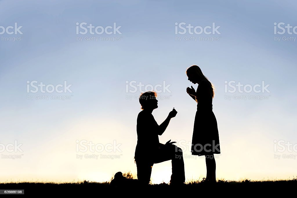 Silhouette of Young Man with Engagement Ring Proposing to Woman stock photo