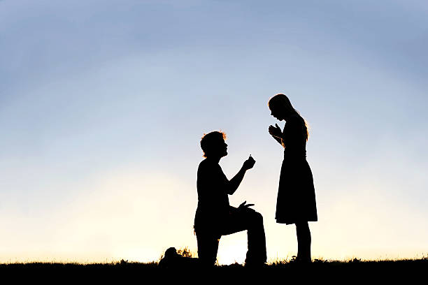 silhouette of young man with engagement ring proposing to woman - noivado - fotografias e filmes do acervo