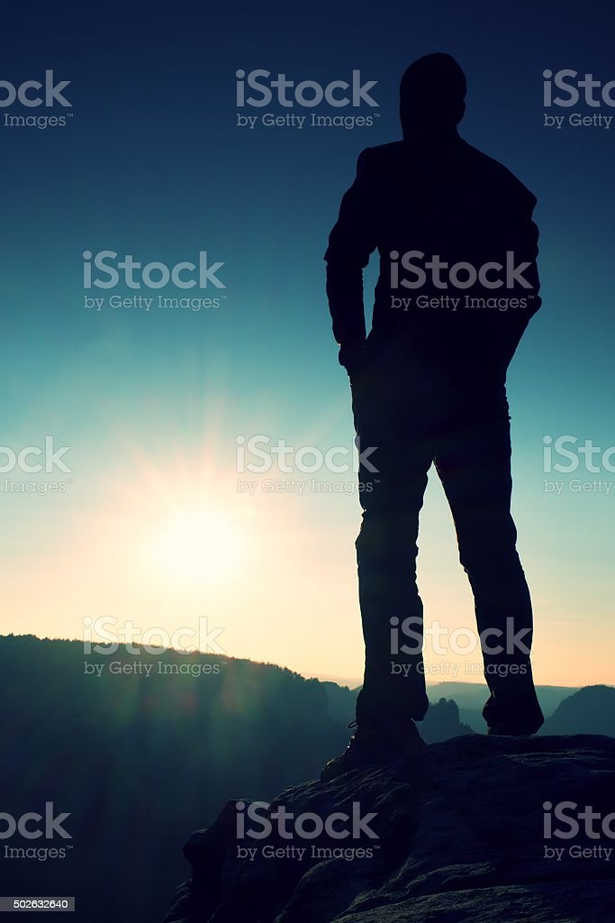 Silhouette of Young Powerful Man Standing with Hands on Hips stock photo