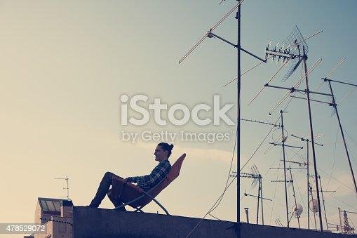 Silhouette of young traveler sitting and resting on the chair on the roof in the city (intentional vintage color)