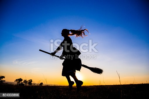 istock Silhouette of young witch flying on the broomstick at sky 824333856