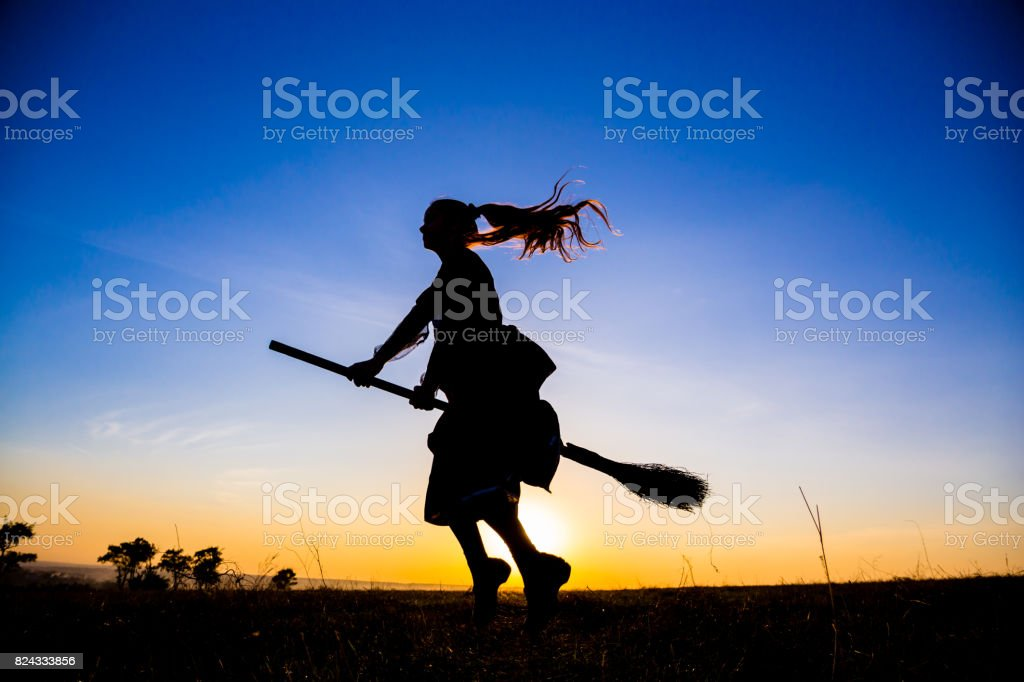 Silhouette of young witch flying on the broomstick at sky stock photo