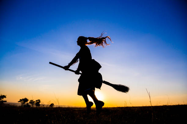 Silhouette of young witch flying on the broomstick at sky Silhouette of young witch flying on the broomstick at blue sky broom stock pictures, royalty-free photos & images