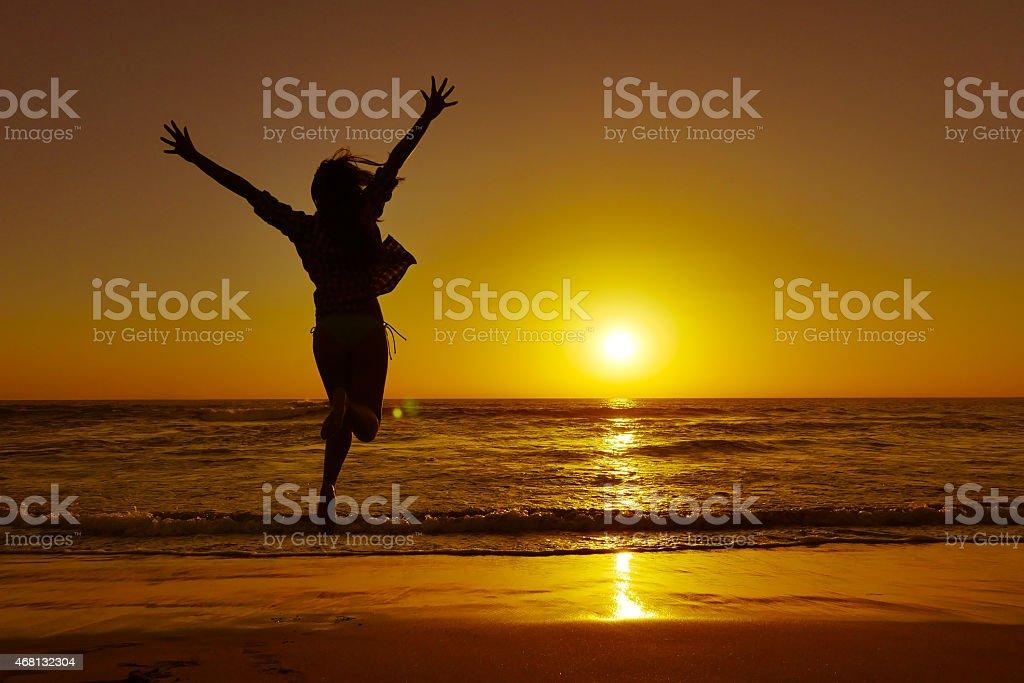 Silhouette de jeune femme sauter avec passion sur la plage au coucher du soleil - Photo