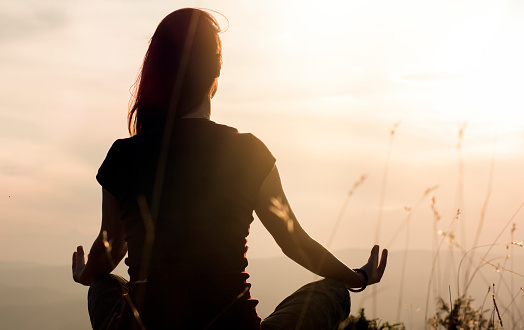 Silhouette of young woman practicing yoga outdoors